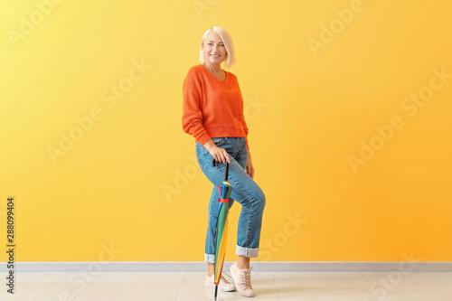 Stylish mature woman with umbrella against color wall Fototapeta