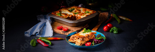 Fototapeta spicy lasagne with tomato sauce and basil obraz