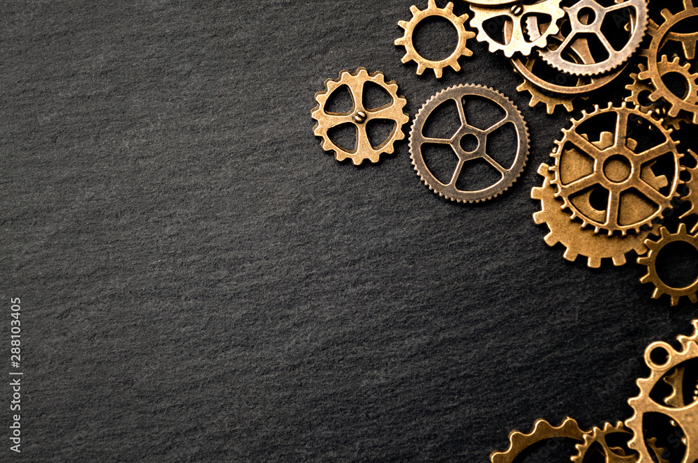 Fototapeta Steampunk accessories and old technology conceptual idea with border made of a group brass cog wheels on dark texture background with copy space