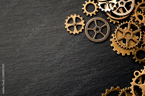 Fototapeta Steampunk accessories and old technology conceptual idea with border made of a group brass cog wheels on dark texture background with copy space obraz