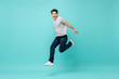 Energetic happy young Asian man in casual clothes jumping