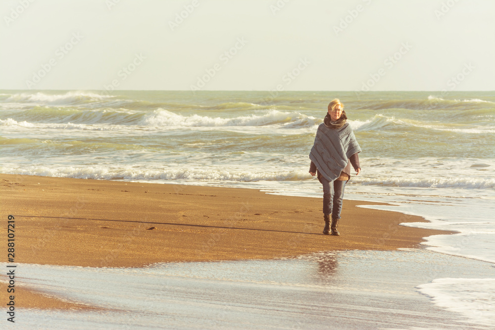 Mature woman with poncho that walks on the seashore in autumn