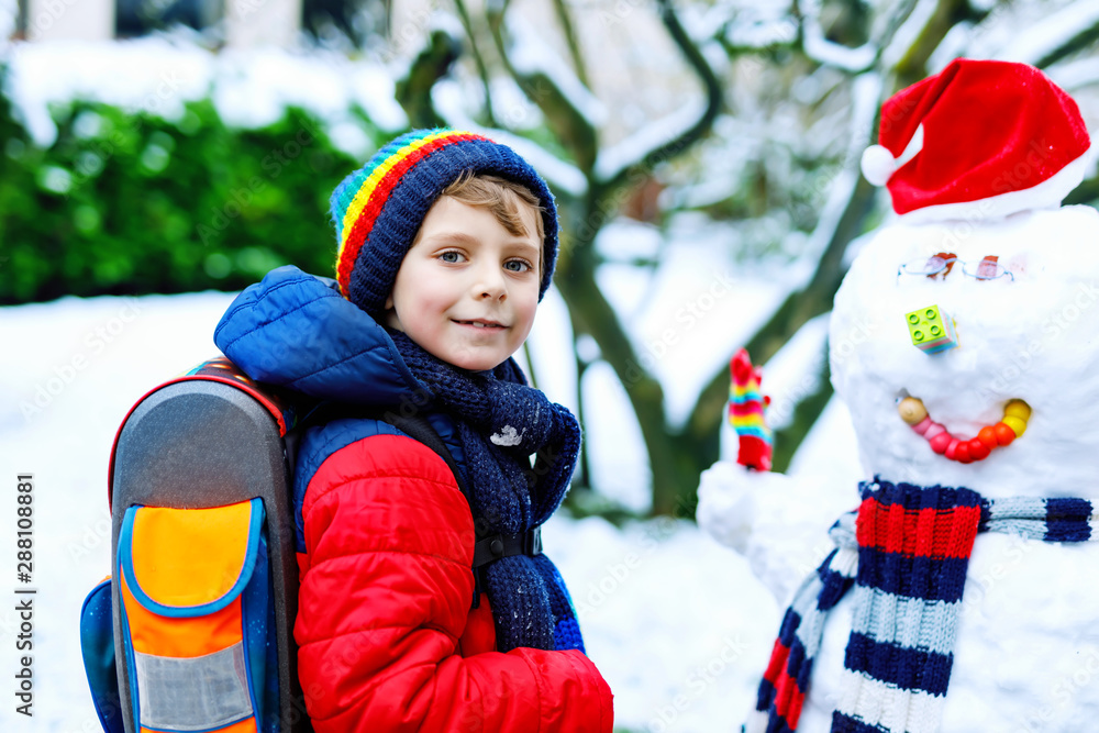Fototapeta Little school kid boy in colorful clothes, with glasses and backpack having fun with snowman after elementary school end