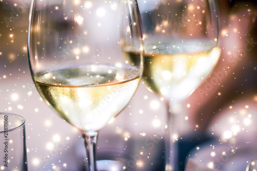 Photo Winter holiday glasses of white wine and glowing snow on background, Christmas t
