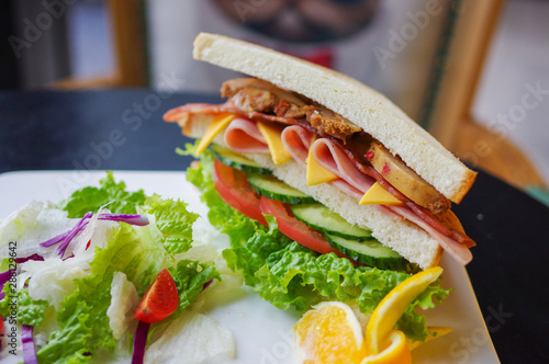 Staande foto Snack Sandwich with ham cheese baked chicken breast lettuce tomato cucumber salad and orange slices on white plate