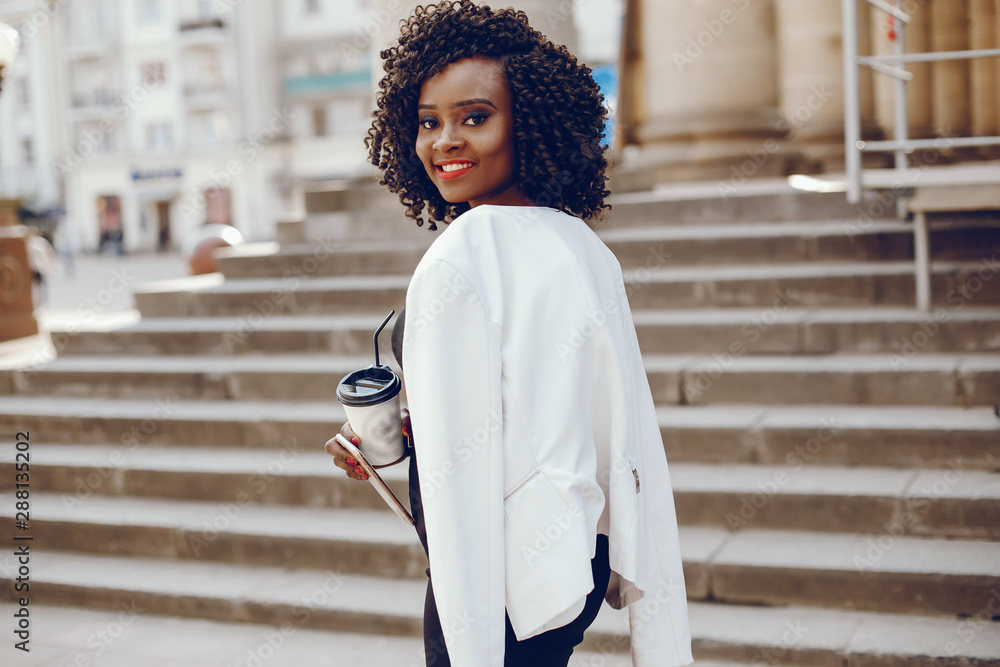 Fototapeta elegant and stylish dark-skinned girl with curly hair and in a white jacket walking around the summer city with coffee and using the phone