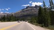 Timelapse point of view of the driver driving on the highway through the Rocky Mountains on a clear summers day