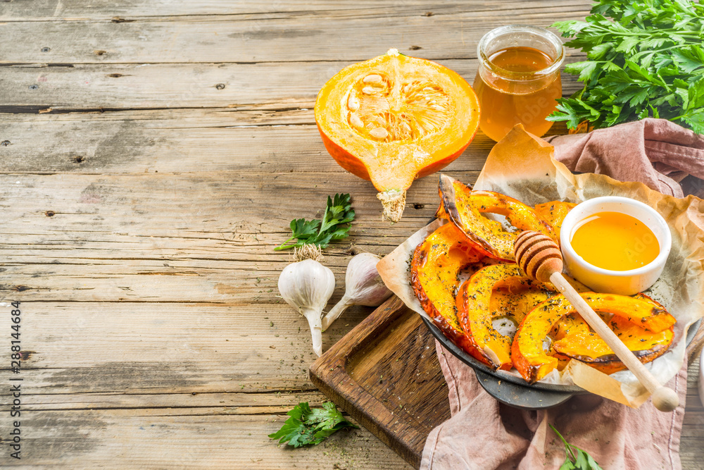Fototapety, obrazy: Autumn vegetarian food recipe. Organic roasted vegetables, Baked fried Hokkaido pumpkin with olive oil, herbs, garlic and honey. On wooden rustic background, copy space