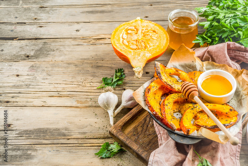 Türaufkleber Natur Autumn vegetarian food recipe. Organic roasted vegetables, Baked fried Hokkaido pumpkin with olive oil, herbs, garlic and honey. On wooden rustic background, copy space