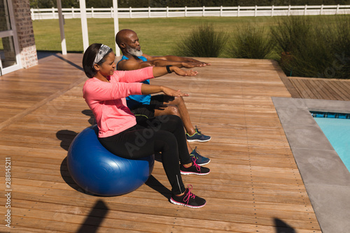 Senior couple performing balancing on exercise ball in the backyard