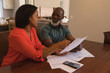 Senior couple discussing over invoices at home