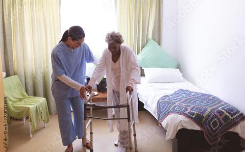 Carta da parati Female nurse helping senior female patient to stand with walker