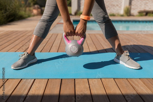 Obraz Woman exercising with kettlebell in the backyard of home - fototapety do salonu