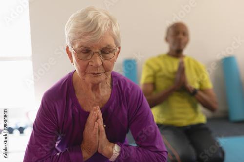 Senior woman doing yoga in fitness studio
