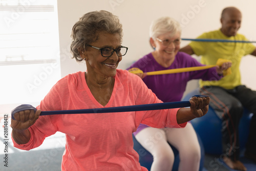 Senior woman exercising with resistance band in fitness studio