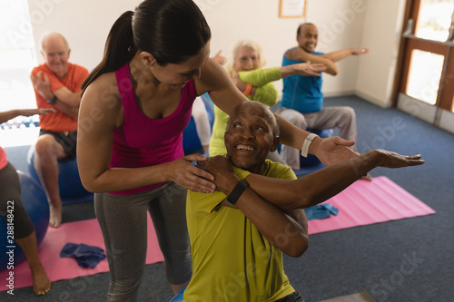 Young female trainer assisting senior man in fitness studio