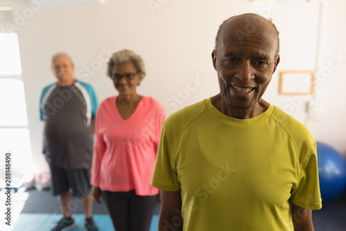 Front view of senior friends looking at camera in fitness studio