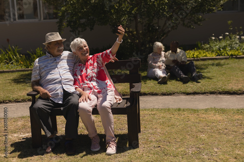 Front view of senior couple taking selfie with mobile phone in garden
