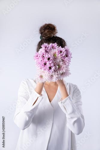 Women behind pink flowers bouquet