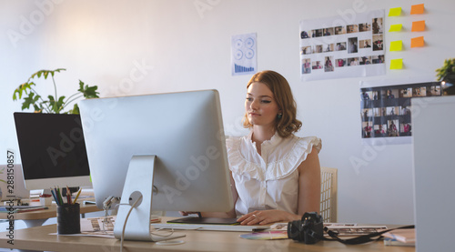 Female graphic designer working on graphics tablet and computer at desk