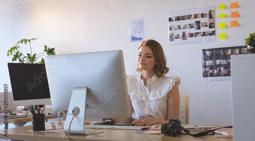 Fotografía  Female graphic designer working on graphics tablet and computer at desk