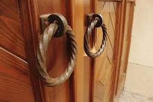 Old And New Iron Ring Door Knockers On Wooden Door
