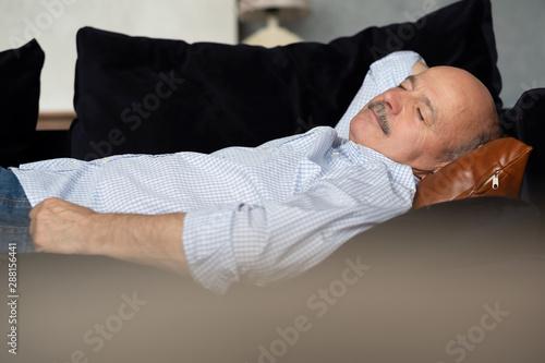 Fototapeta Tired senior hispanic man sleeping on dark blue couch, taking afternoon nap at the living room obraz