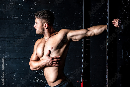 mata magnetyczna Young sweaty muscular strong fit man stretching his arm and chest muscles after heavy and hard workout training in the gym real people