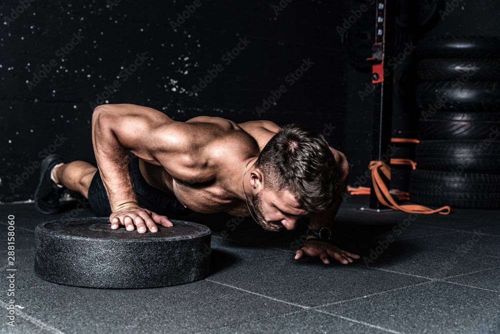Fototapety, obrazy: Young strong sweaty focused fit muscular man with big muscles doing push ups with one hand on the barbell weight plate for training hard core workout in the gym real people selective focus
