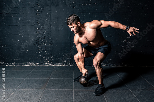 Young strong sweaty focused fit muscular man with big muscles holding heavy kett Fototapeta