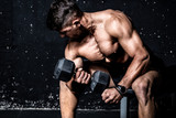 Young strong muscular sweaty man biceps muscle crossfit workout training with heavy dumbbell in the gym dark image with shadows real people