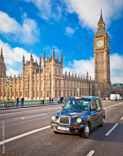 London, UK; circa Dec 2012: Famous Black Cab crosses Westminster Bridge in Front of the Houses of Parliament