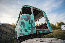 The Back Of An Old Abandoned Green Bus In A Field