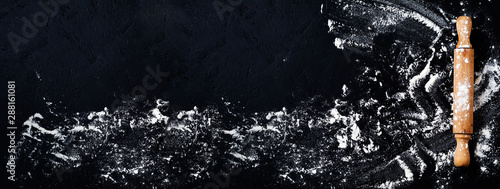 Rolling pin with flour on dark black baking background, top view, copy space for text, menu, recipe Fotobehang