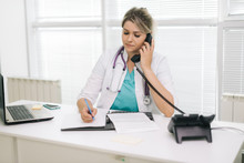 Portrait Of Young Woman Doctor In White Uniform Sitting At The Table And Writing A Prescription In Document While Talking On The Phone At Office. Girl Doc Sitting Against The Background Of A Window