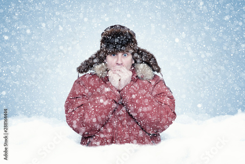 Fotografie, Obraz  Frozen man in red winter clothes stands waist-deep in a snowdrift and warms his