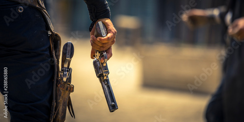 Man holding his six-shooter ready for a gunfight, Western movie set Wallpaper Mural