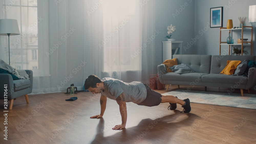 Fototapety, obrazy: Muscular Athletic Fit Man in T-shirt and Shorts is Doing Push Up Exercises at Home in His Spacious and Sunny Living Room with Modern Interior.