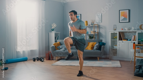Fototapeta Strong Athletic Fit Man in T-shirt and Shorts is Energetically Jogging in Place at Home in His Spacious and Bright Living Room with Minimalistic Interior. obraz