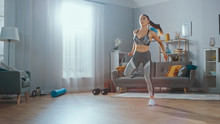 Strong And Beautiful Athletic Fitness Girl In Sportswear Is Doing Cardio Exercises In Her Sunny And Spacious Living Room With Minimalistic Interior.
