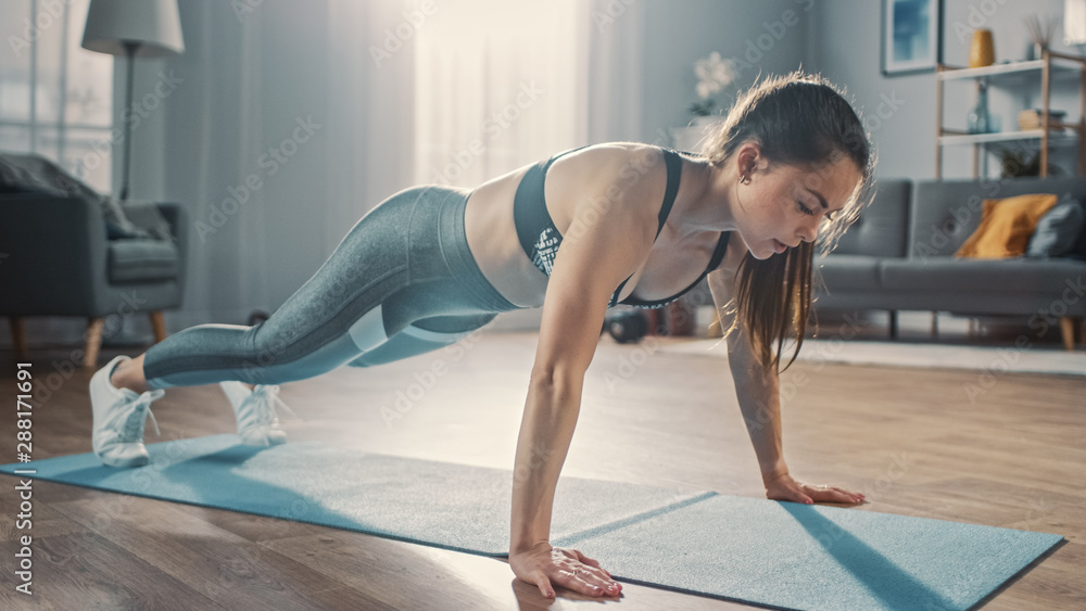 Fototapety, obrazy: Strong Confident Beautiful Fitness Girl in Grey Athletic Sportswear is Doing Push Up Workout Exercises in Her Bright and Spacious Apartment with Cozy Minimalistic Interior.