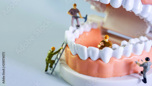 Photo Small figure worker cleaning tooth model as medical and healthcare concept, Regular checkups are essential to oral health