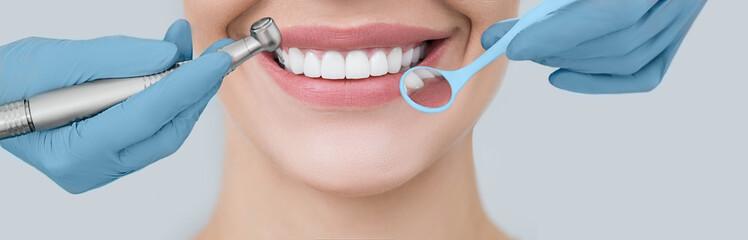 Przycięty idealny uśmiech i dłonie dentysty trzymające wiertło dentystyczne i lusterko kątowe. Stomatologia i leczenie zębów