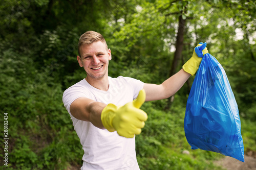 Valokuva Portrait of cheerful male volunteer with garbage bag