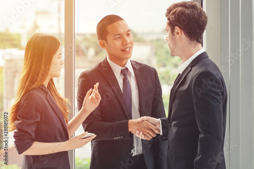 Fotografía  Two businessmen shaking hands with a woman translator standing on the side