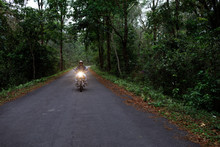 Handsome Man Riding A Motorbike On A Forest Road