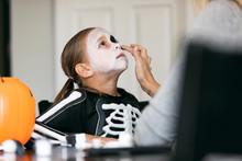 Skeleton: Mother Applying Black Makeup Around Eyes Of Girl