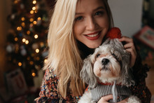 A Woman In Her Twenties Celebrating Christmas With Her Small Dog At Home