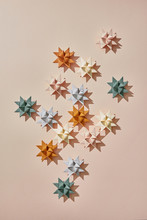 Christmas Multicolored Paper Origami Stars On A Dark Beige Background With Space For Text. Flat Lay