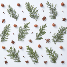 Natural Pattern Of Green Branches, Acorns, Anise Stars And Cloves Spices On A Gray Background. Christmas Card Concept. Flat Lay